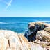 Cliff rocks by trail by Portland Head Lighthouse in Fort Williams park in Cape, Elizabeth Maine during summer day