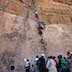 Orthodox Christian pilgrim men being hauled up a 15m cliff face by monks to reach the mountain-top church and monastery of Debre Damo, Northern Tigray province, Ethiopia.