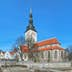 Tallinn, Estonia - March 19, 2015: St. Nicholas Church (Niguliste kirik) and cupola of Alexander Nevsky Cathedral. The St. Nicholas Church was founded and built around 1230-1275. Today it houses a branch of the Art Museum of Estonia.