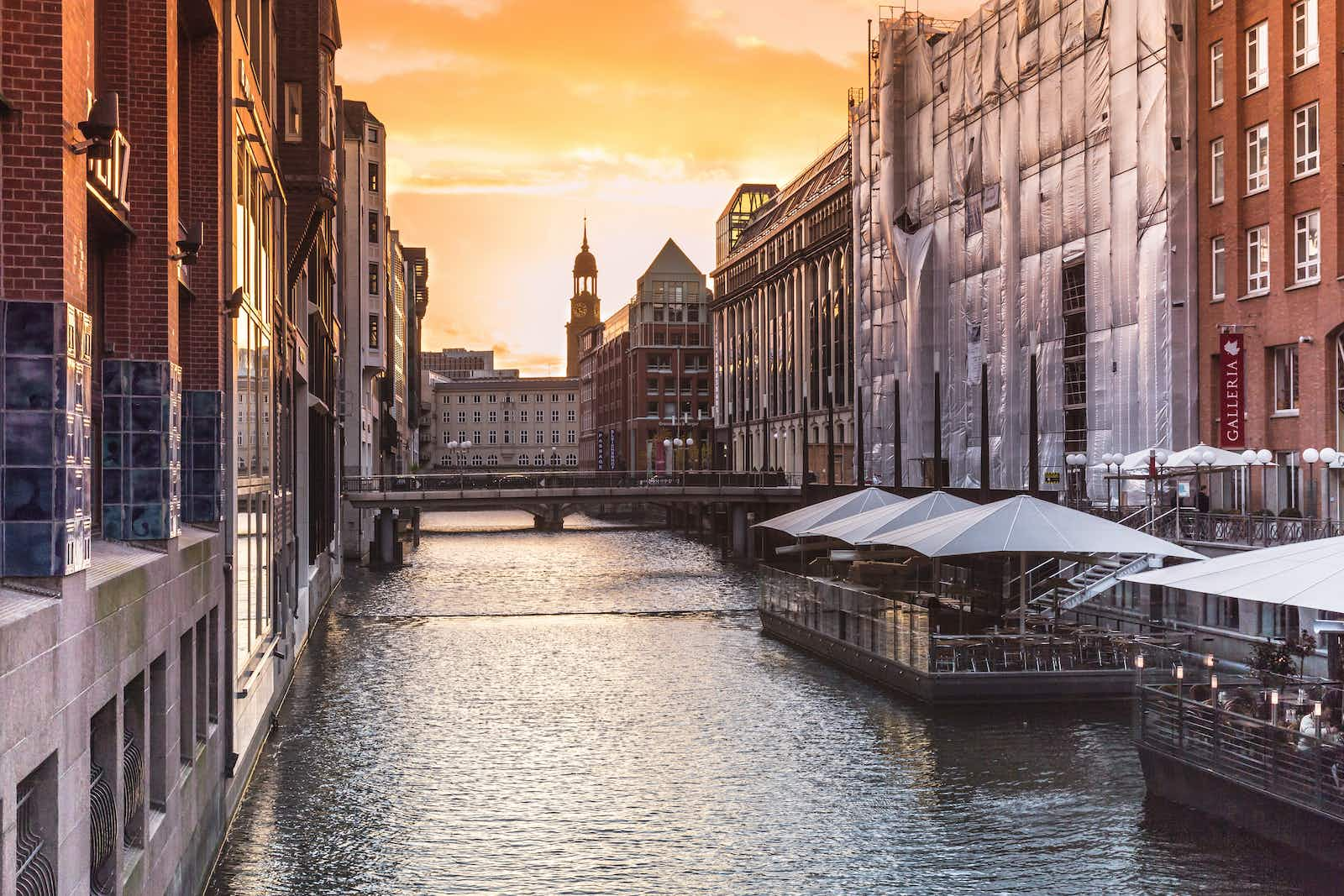 A view down the river in Hamburg with tall beautiful architecture on either side and the sun setting behind it; Copenhagen alternatives