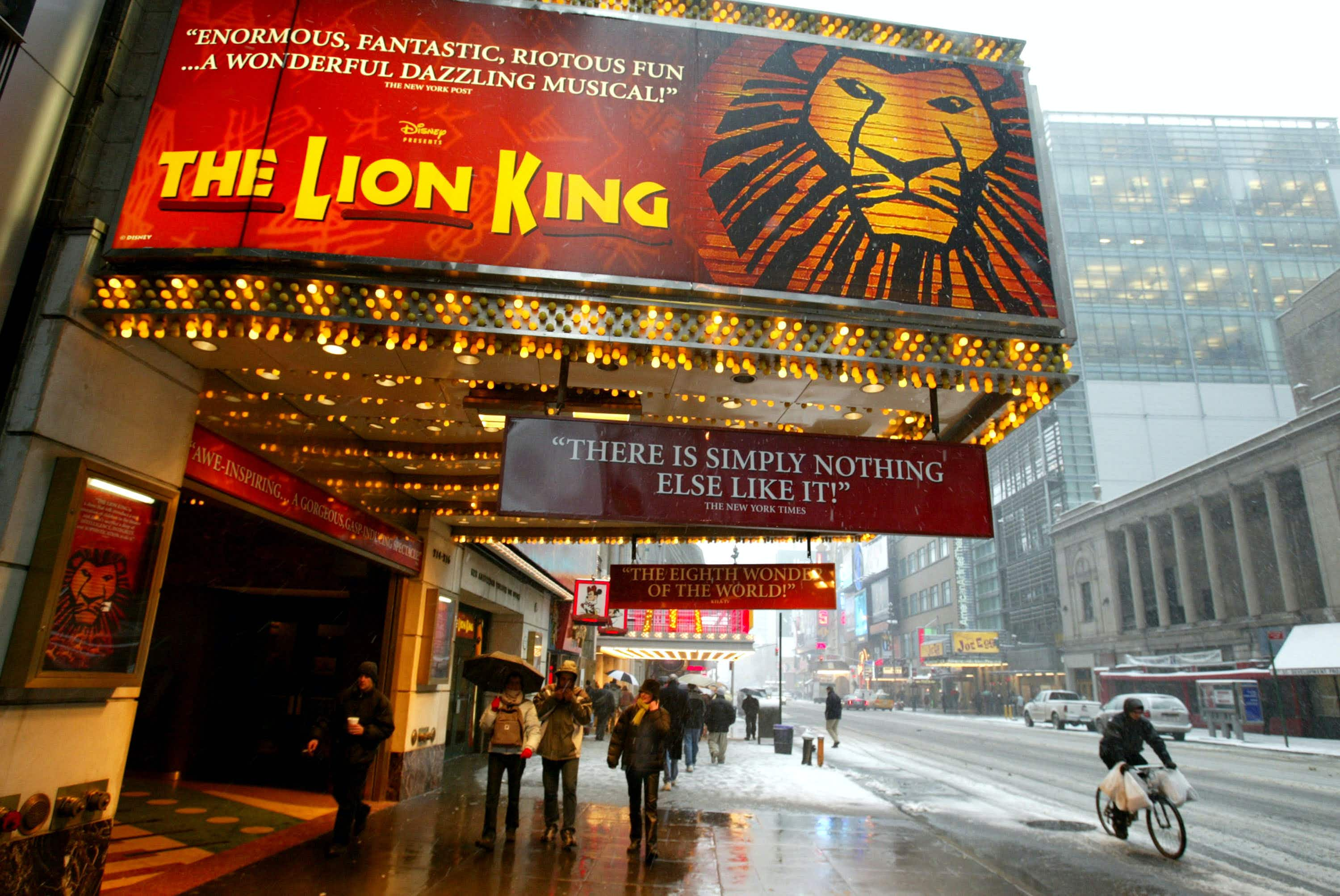 """NEW YORK - MARCH 6:  Pedestrians walk beneath a sign for the musical """"The Lion King"""" March 6, 2003 in New York City. About 325 Broadway theater musicians are set to go on strike tonight at midnight unless an agreement on orchestra size can be reached.  (Photo by Mario Tama/Getty Images)"""