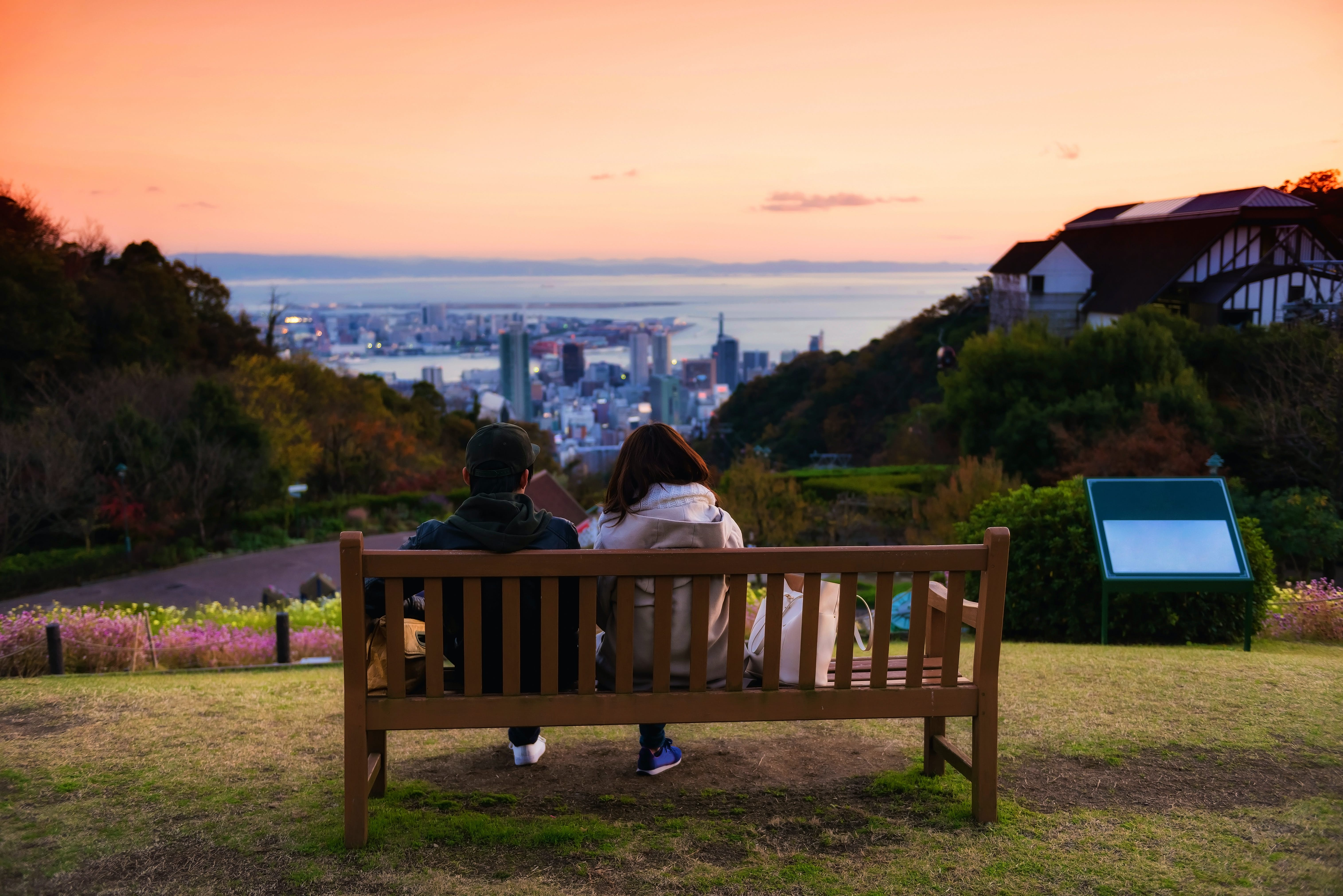 Sweet young couple sitting on wooden chair seat to enjoy aerial view of Kobe Nunobiki Herb Gardens and skyline cityscape with twilight sky at dusk, Japan.