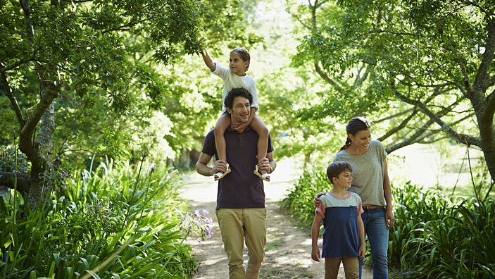 Full length of two generation family walking on path in park