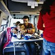 Father sitting with son at table in camper van cutting pancakes during breakfast