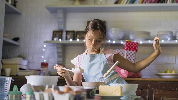 Girl is dancing while baking. Child is preparing food in kitchen. She is wearing apron.