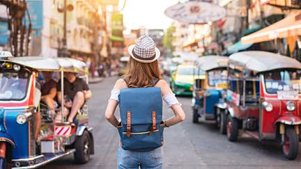 The back of a young woman walking and walking along the pedestrian street in the evening in Bangkok, Thailand, travelers and tourists.