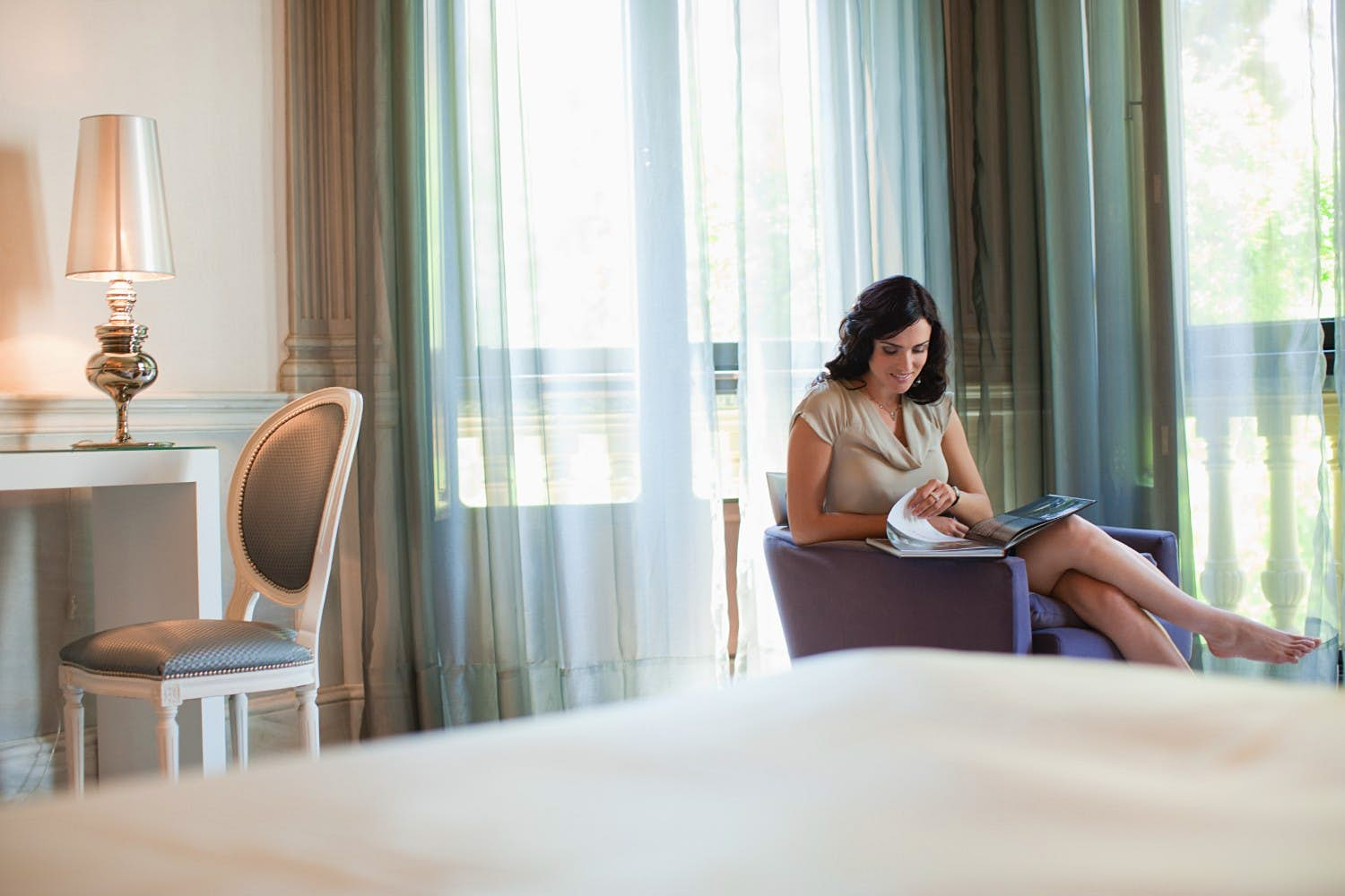 A woman reading a magazine in a hotel room