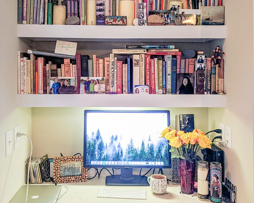 A home office setup that consists of a desk under a bookshelf full of colorful volumes. A vase of yellow roses sits on the desk next to a computer monitor, keyboard, mouse, and laptop, surrounded by framed photos and mementos