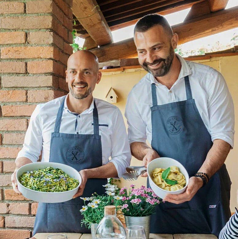 Two chefs holding pasta dishes