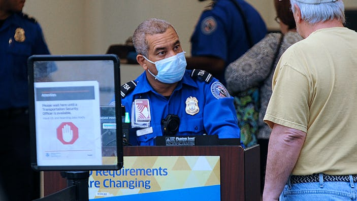 ORLANDO, FLORIDA, UNITED STATES - APRIL 2, 2020: A TSA officer wears a protective mask while screening travellers at Orlando International Airport. In the past 14 days across the nation, 58 TSA screening officers have tested positive for COVID-19, includi
