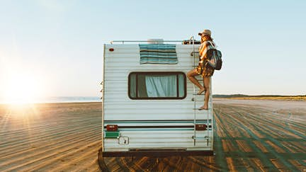 Young woman on the back of an RV, which is parked on the beach during sunset.