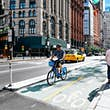 June 20, 2018: Cyclist riding in a bike lane at the Park Row financial district.