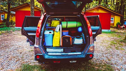 Camping luggage tightly packed into a car trunk in a forest setting.
