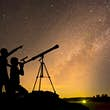 Silhouette of children looking through a telescope at the Milky Way galaxy.