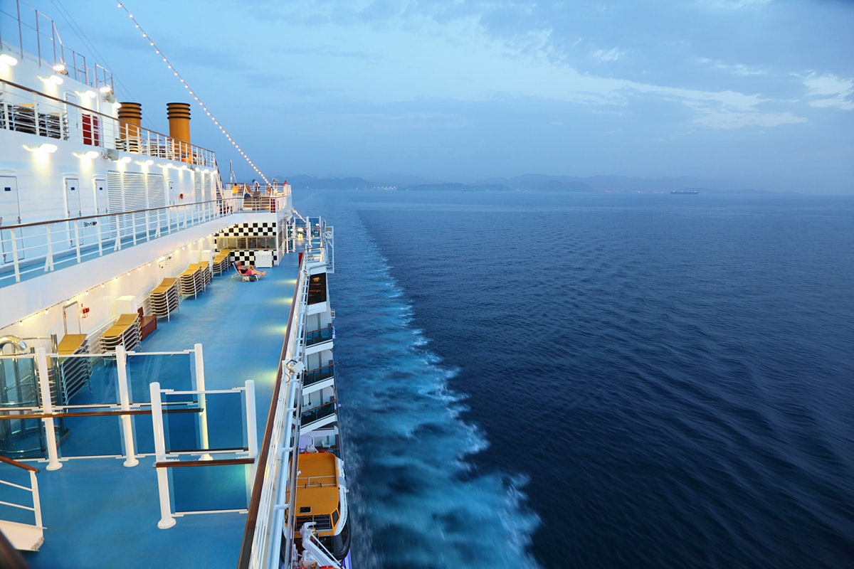 The deck of a cruise ship during the evening.