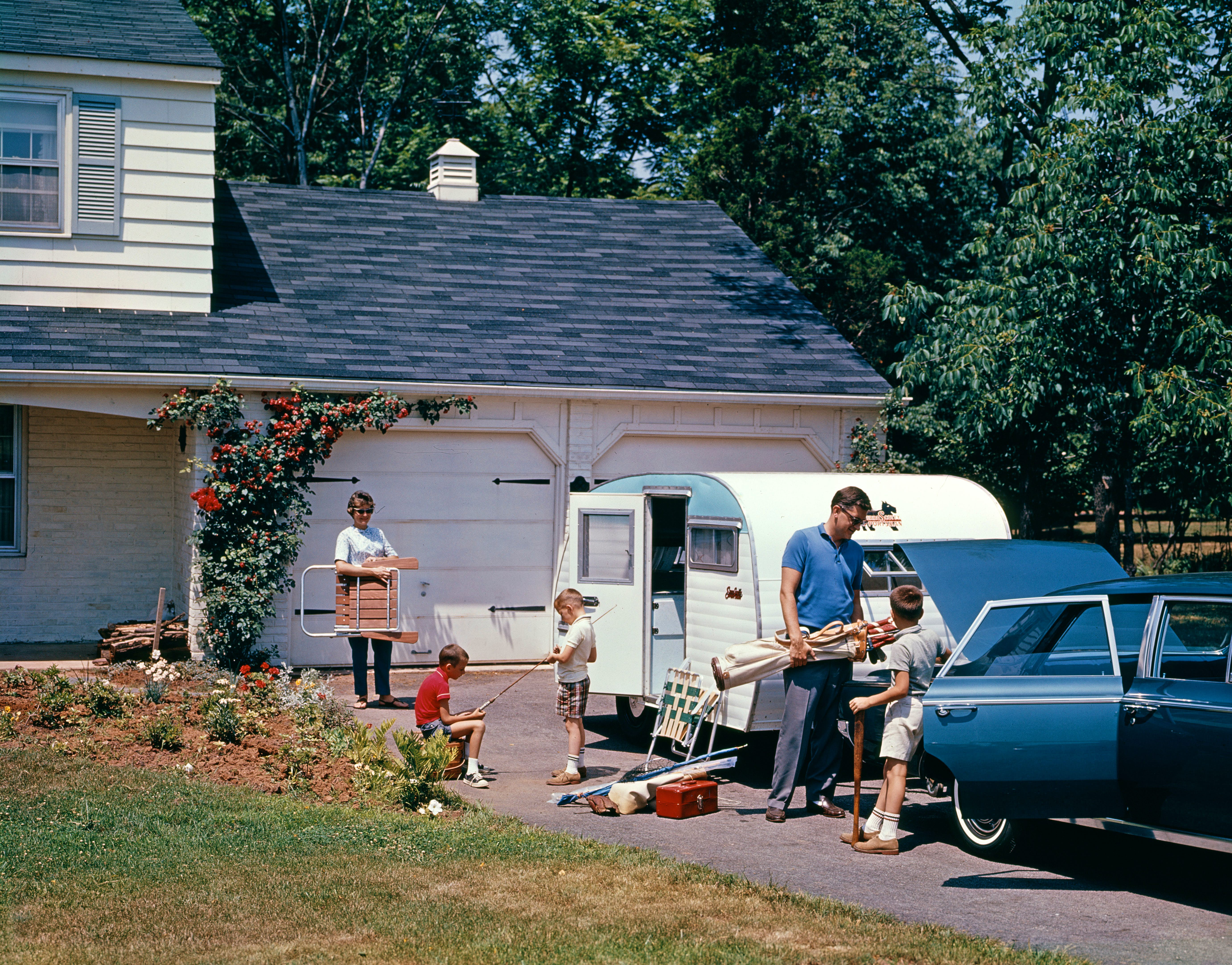 1960s FAMILY FATHER MOTHER SON DAUGHTER LOADING CAR AND TRAILER FOR VACATION SUMMER OUTDOOR