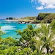 Hawaii, Maui, Tropical Hamoa beach in Hana with palm trees and blue sky.