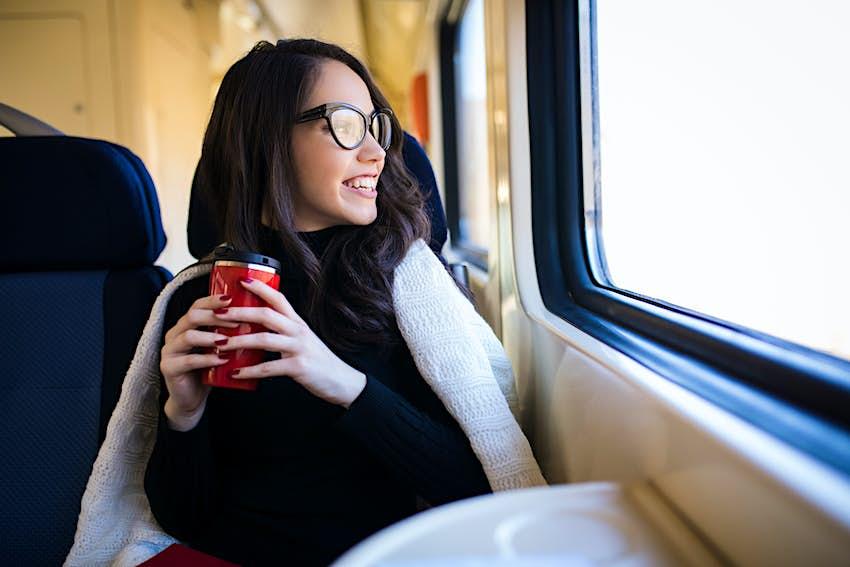 Young beautiful woman looking through the train window.