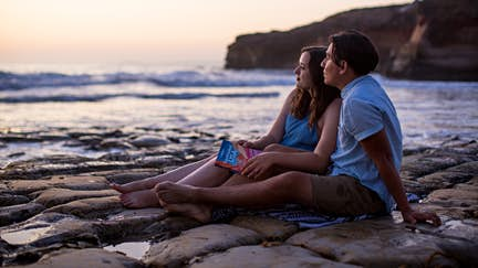 Couple on rock shelf on beach with LP Southwest USA guidebook.