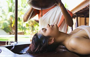 A woman receives the Ayurvedic shirodhara therapy at a resort in India