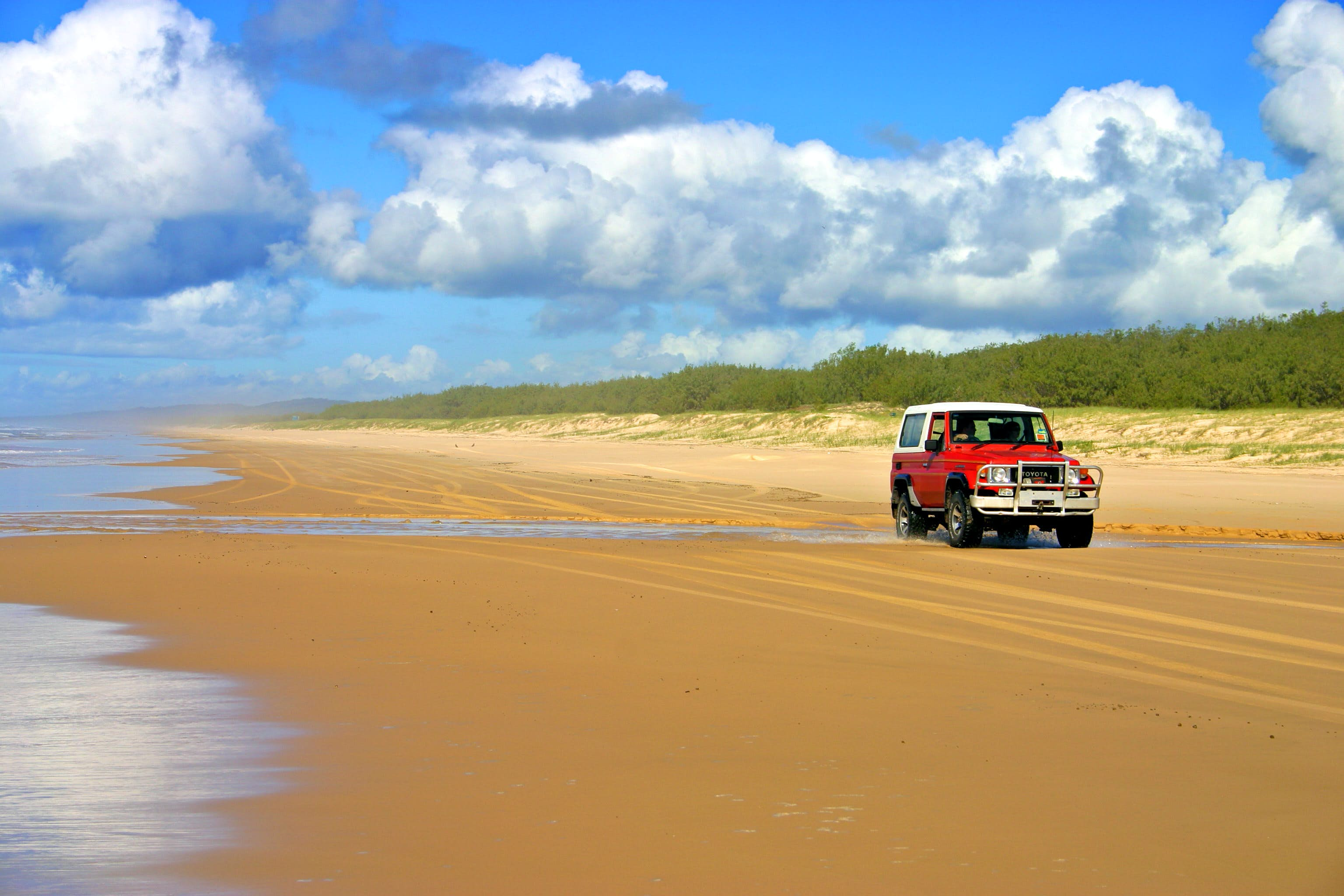 A red truck cruises on the sands on Fraser Island, Australia