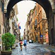 ROME, ITALY - AUGUST 31, 2016: tourist strolling along Via Giulia under Arco Farnese in the historic center of Rome, Italy