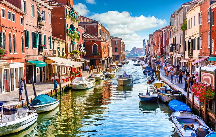 Visitors and boats in the canals of Murano Island