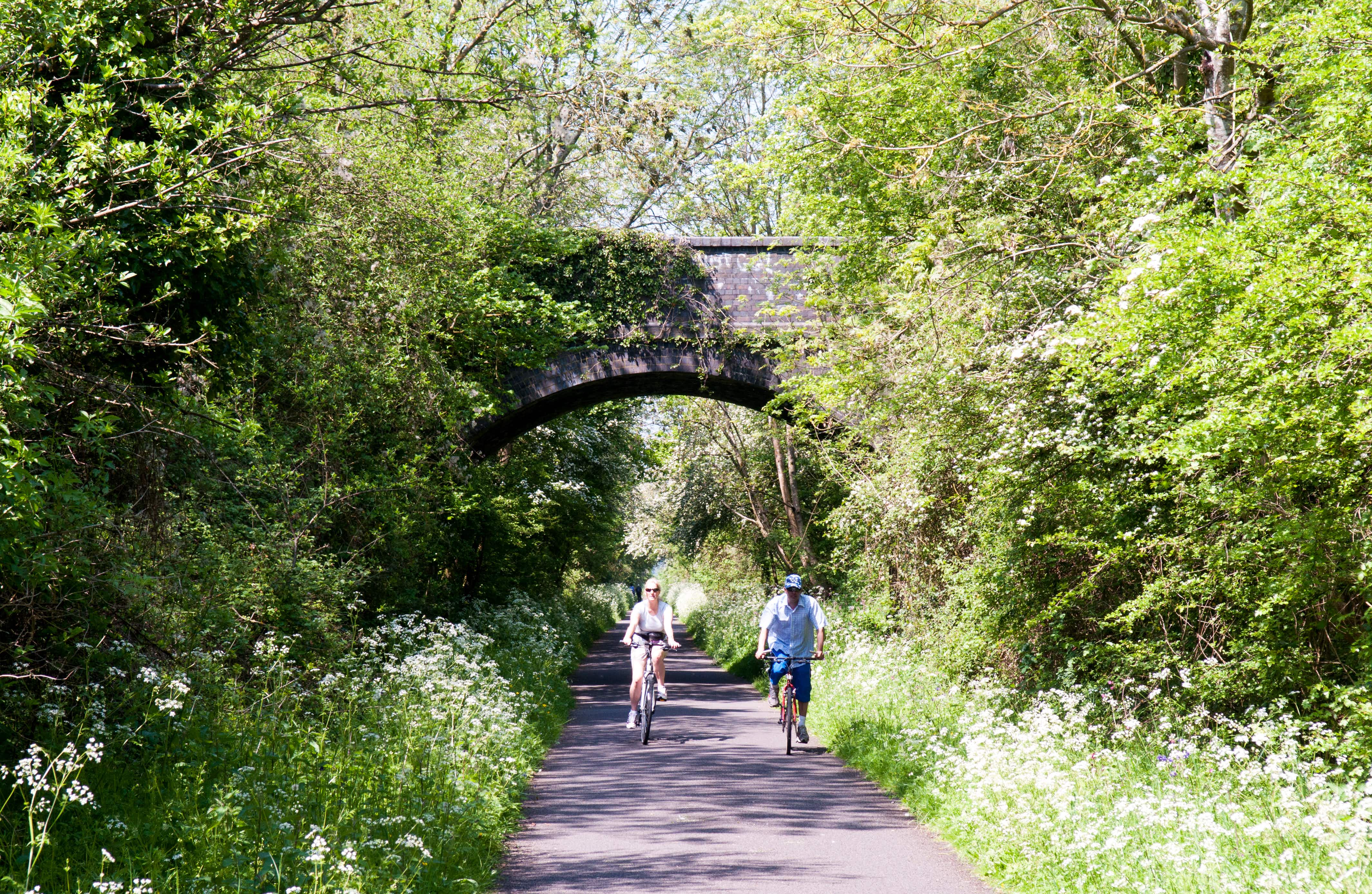 Bath, England - May 22, 2012: A couple cycling on the Bristol and Bath Railway Path in spring.