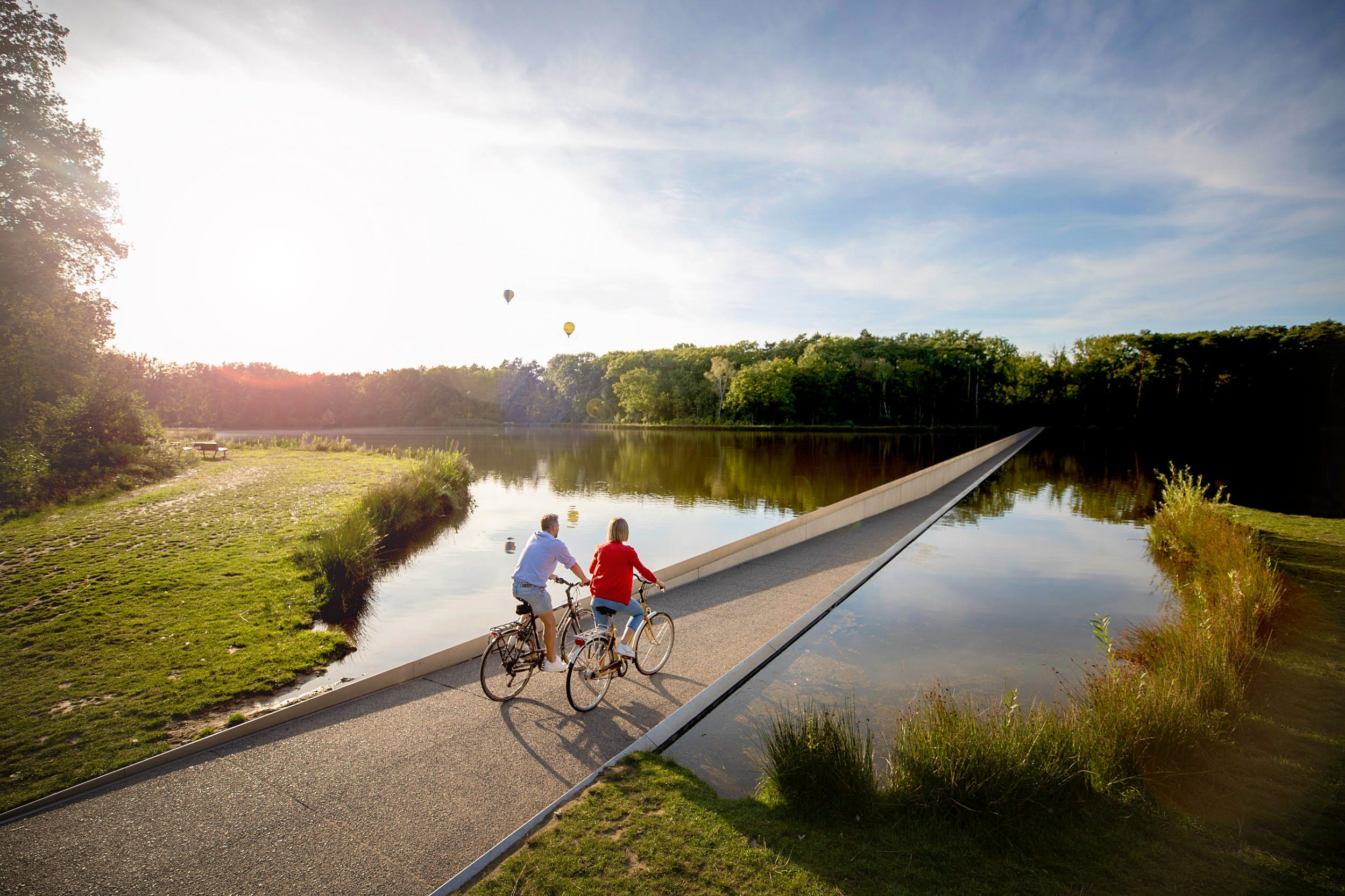 Two people cycling on a path through a pond