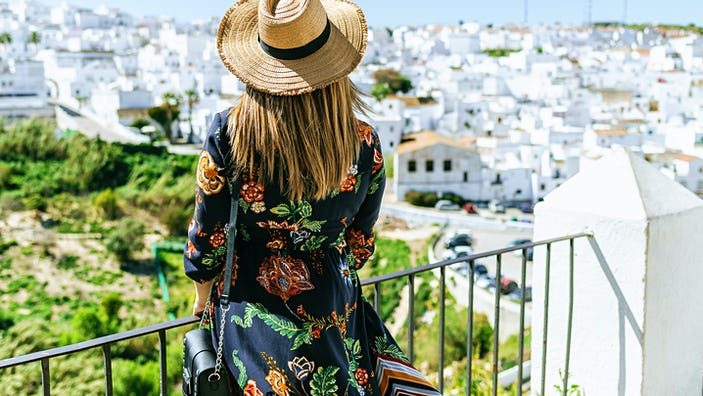 Fashionable woman on roof terrace looking at the white buildings of Vejer de la Frontera.