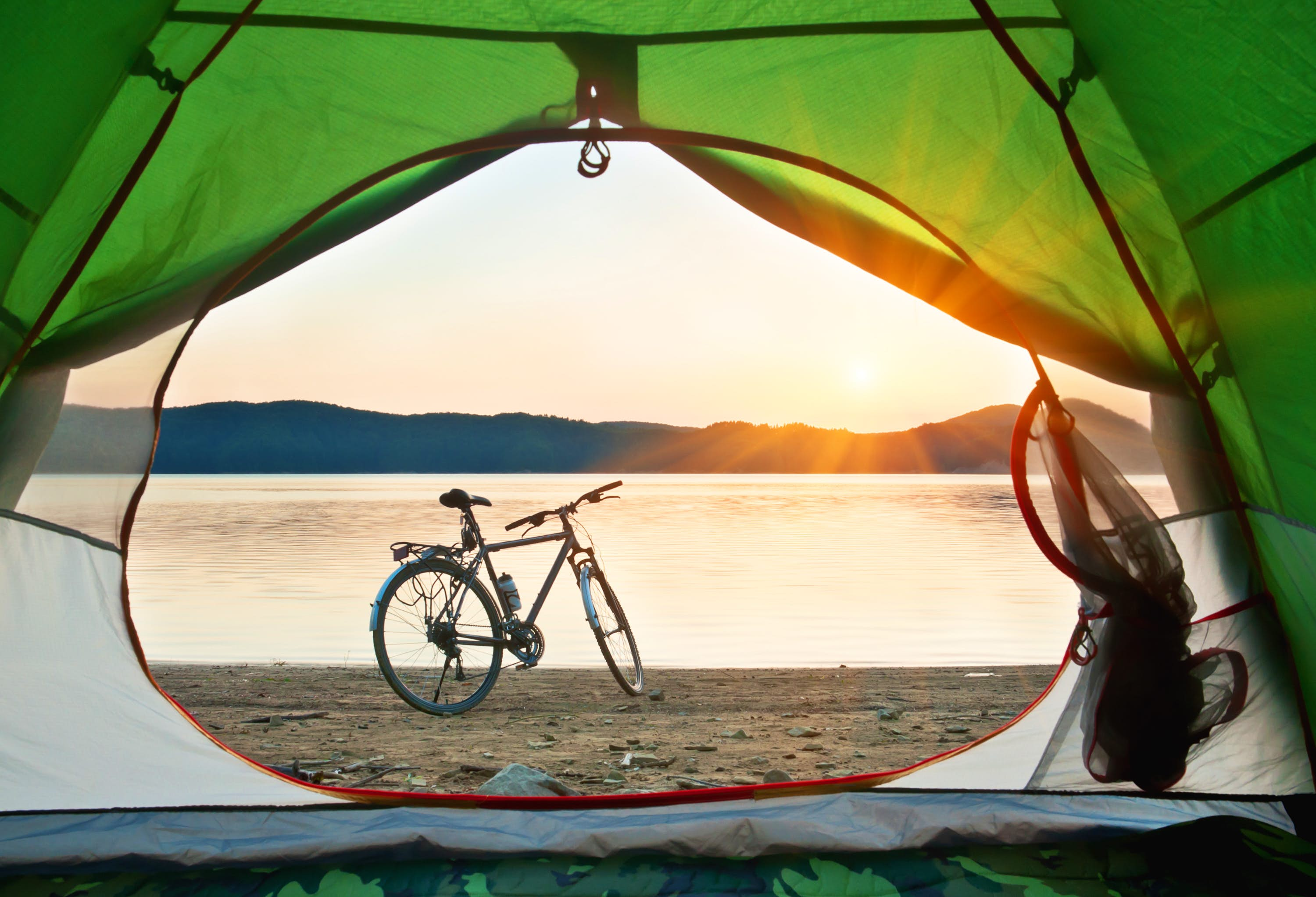 A bicycle on the shore of some water, viewed through the opening in a tent