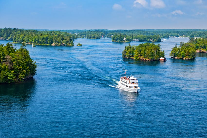 An aerial shot of a tour boat cutting through a vast body of water littered with greenery-covered islands
