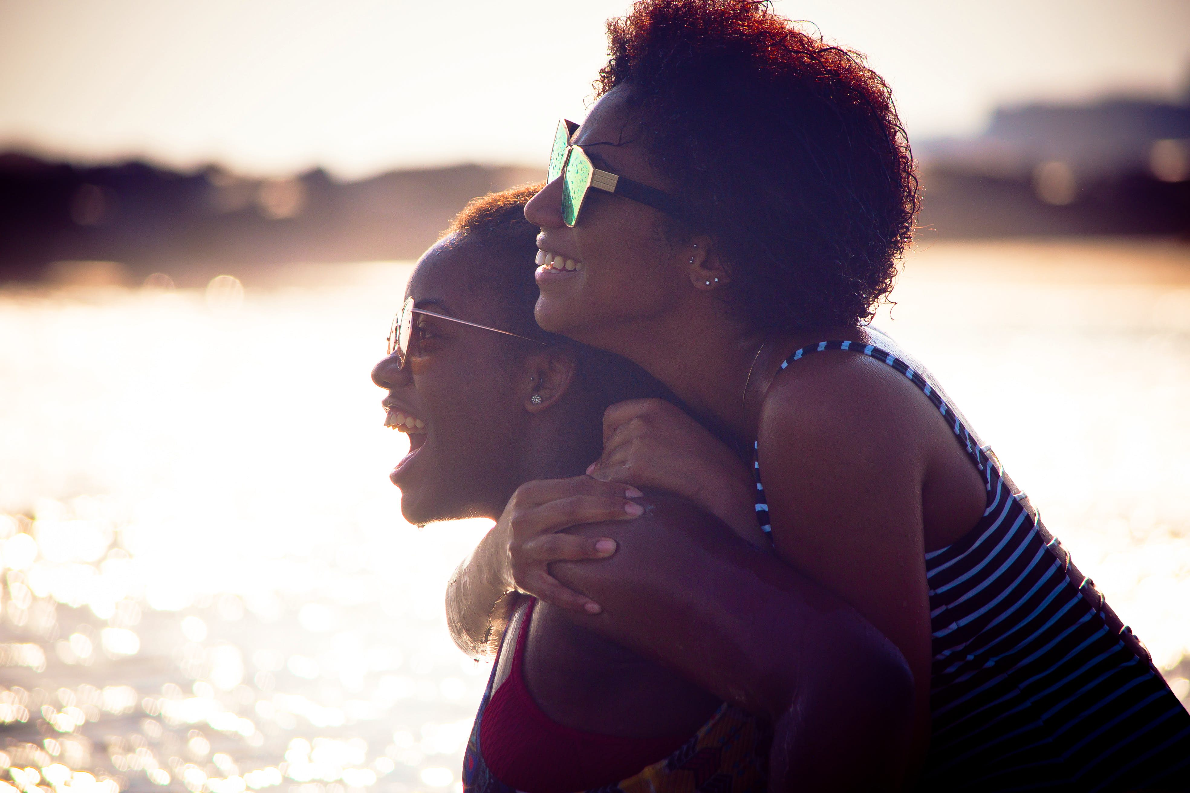 Two black women hug and smile at the beach together.