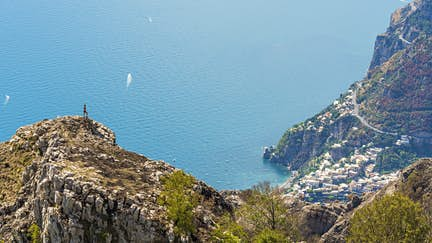 A hiker looking at the Amalfi Coast and the town of Positano.