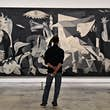 MADRID, SPAIN - JUNE 06: A man looks at Guernica by Pablo Picasso during the partial reopening of the Reina Sofia Museum, after its closure in March due to the Covid-19 pandemic, on June 06, 2020 in Madrid, Spain. A maximum of 30 people (30%) at a time ar