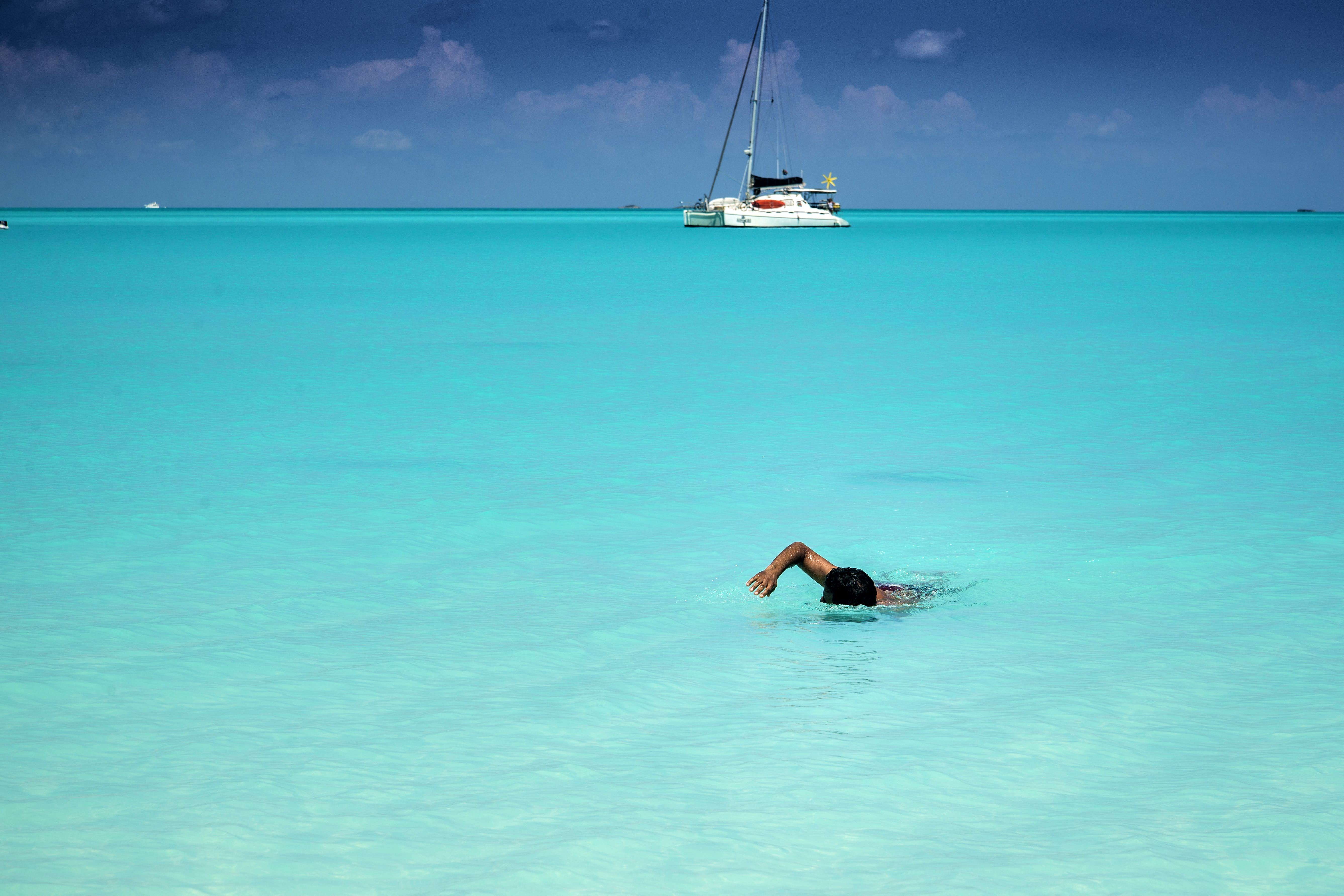 Man swimming to shore in perfectly clear turquoise-colored water. A catamaran sailboat at anchor is in the background