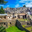 The ancient city of Pompeii with ruined houses and stone streets.
