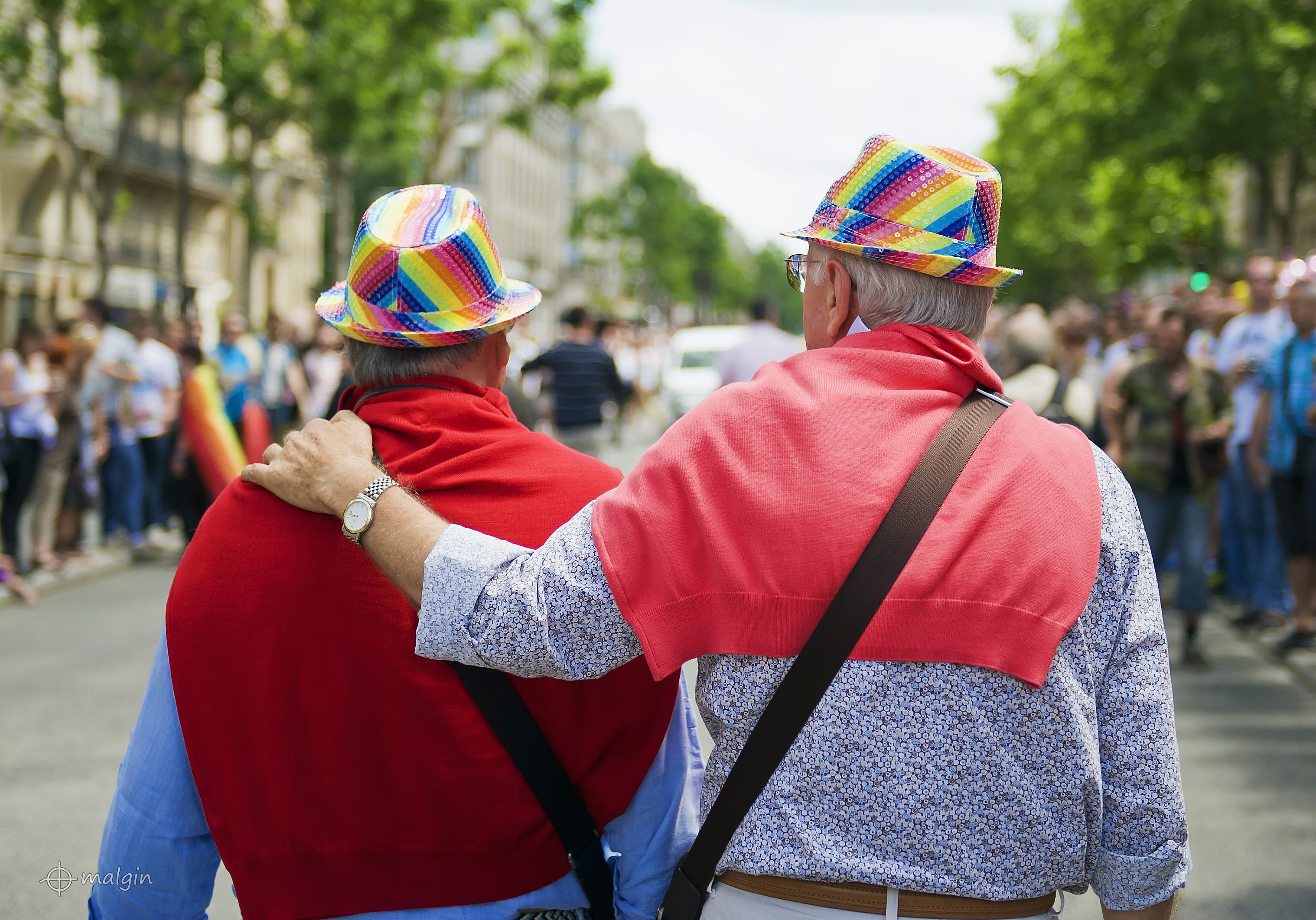 Two men viewed from behind. They're walking along together, one with his arm around the other. Both have red jumpers slung over their shoulders and are wearing rainbow hats