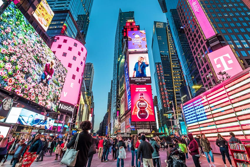 APRIL 23, 2018: The architecture of Times Square with its neon billboards, stores, and many tourists at dusk.