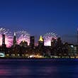 New York City skyline (with the Empire State Building) at night with fireworks in the sky on the Fourth of July.