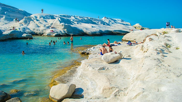 August, 2018: Swimmers and sunbathers at Sarakiniko beach with white volcanic rocks.