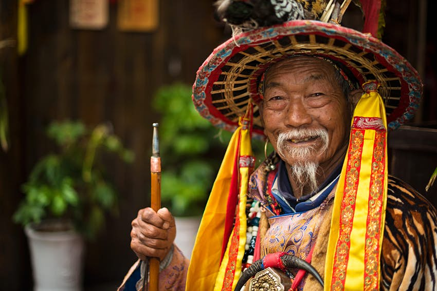 A Naxi nationality old man dressed in ancient Dongba clothing, smiling and welcome the travelers