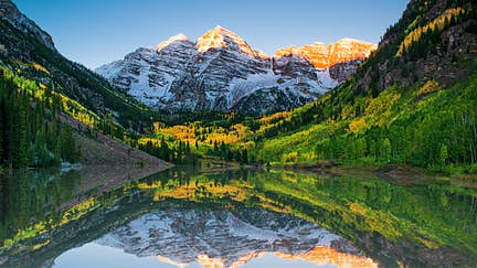 Sunrise and reflections at Maroon Bells lake.