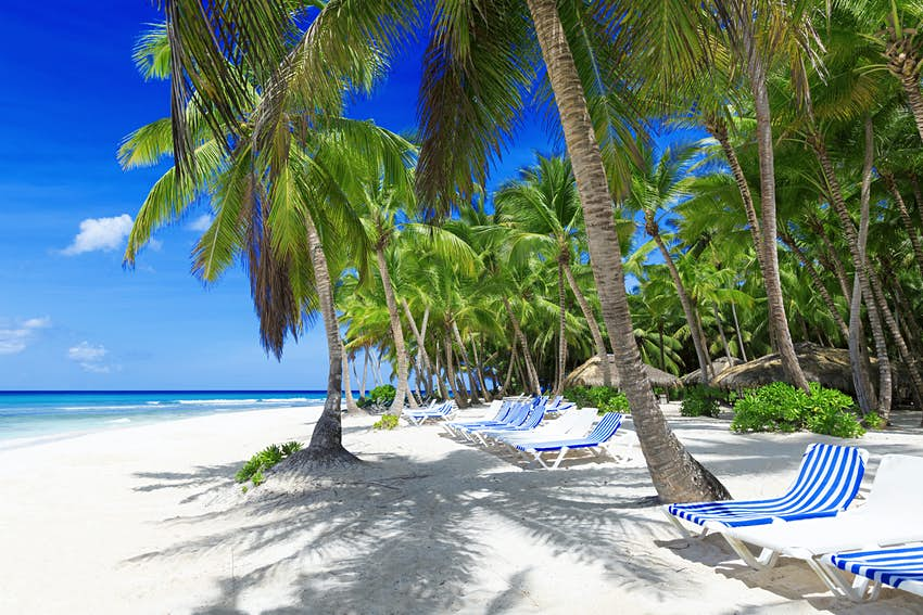 Beach on the tropical island. Clear blue water, sand and palm trees. Beautiful vacation spot, treatment and aquatics