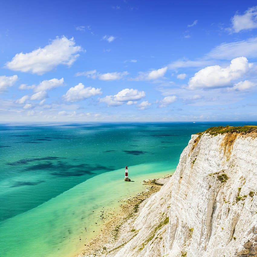 Một vách đá trắng ở rìa biển xanh như ngọc. Một ngọn hải đăng sọc trắng đỏ đứng giữa vùng nông