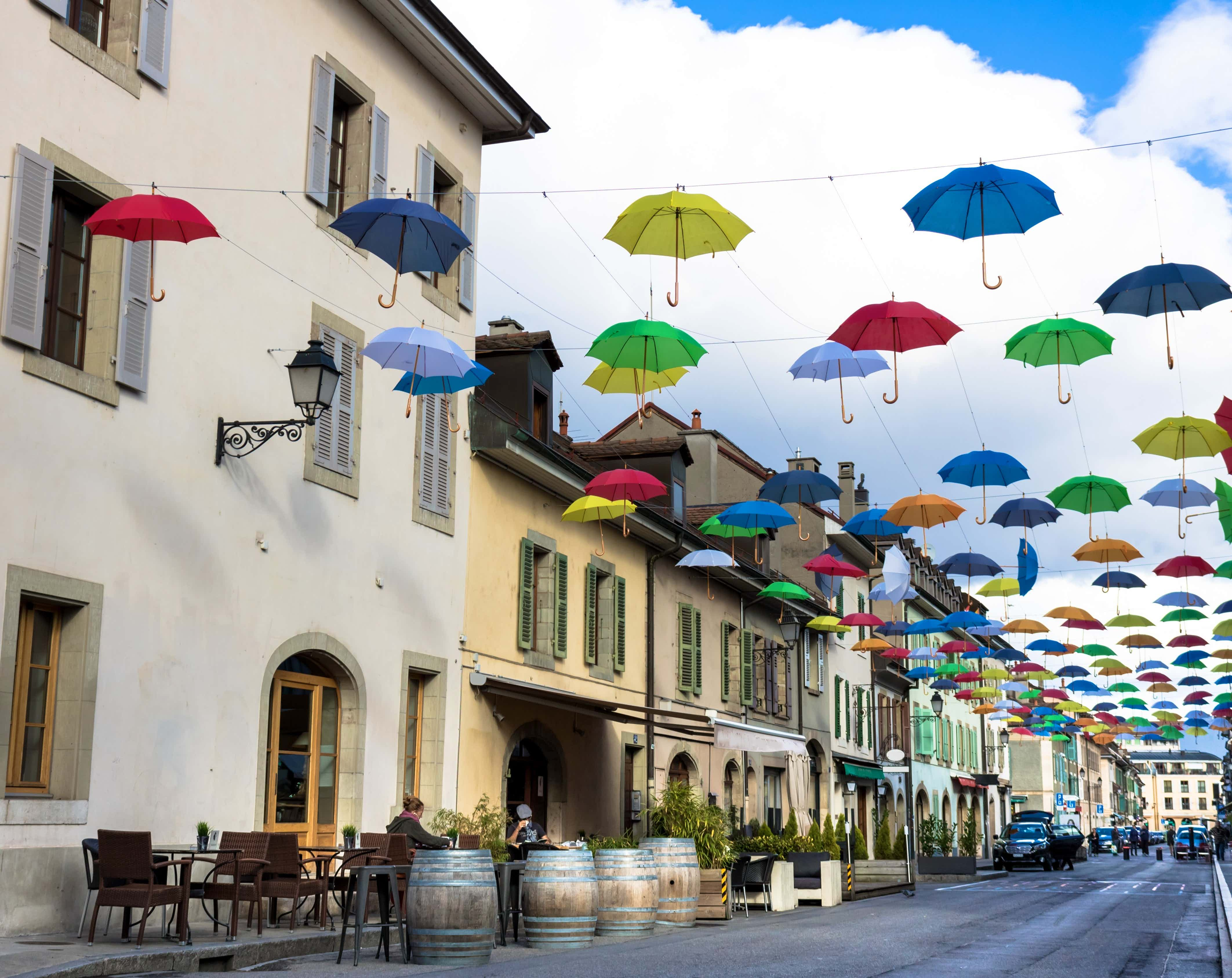 Multicolored umbrellas hang from wires above the street in the Carouge area, Geneva.