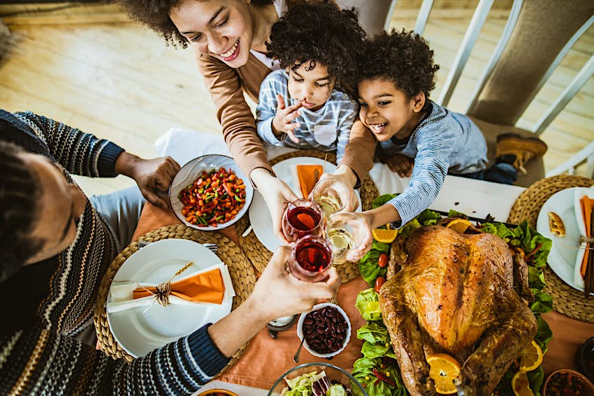High angle view of happy African American family toasting during Thanksgiving lunch at dining table.