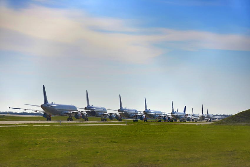 A line of aircraft parked at an airport