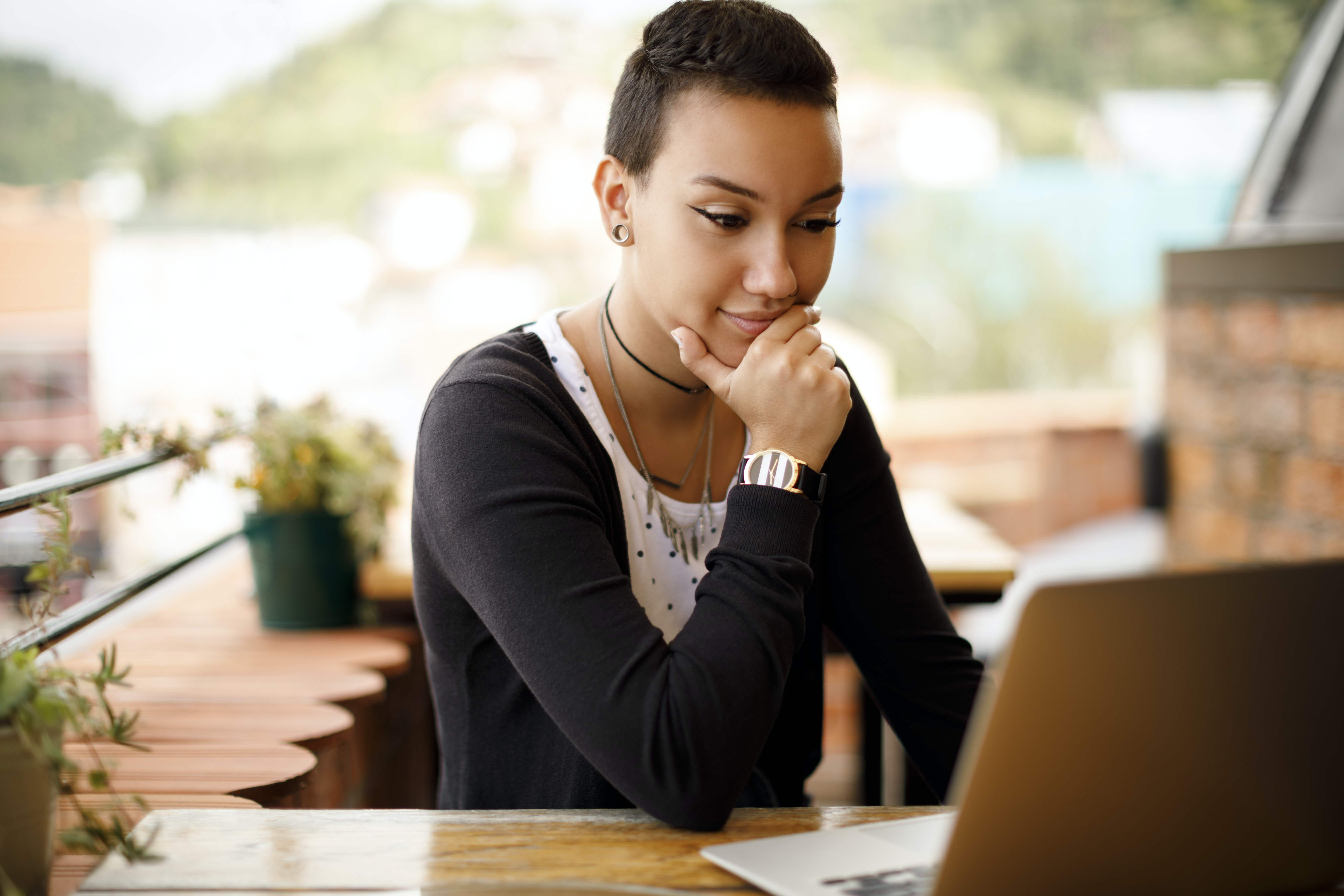 Young woman using laptop at a cafe