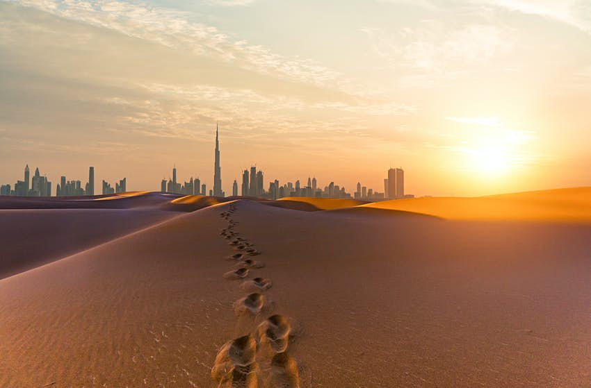 Footsteps in desert sand heading towards skyscrapers of the Dubai city skyline at daw